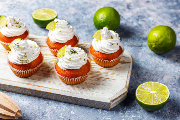 Homemade key lime cupcakes with whipped cream and lime zest,selective focus Free Photo