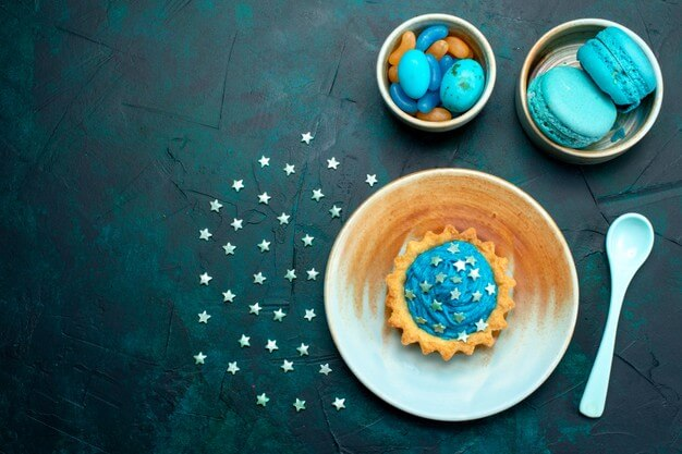 Top view of cupcake with stars decorations next to macaroons and sweets plates Free Photo