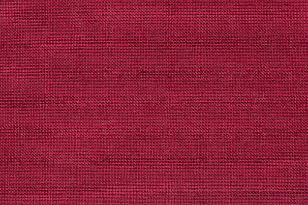 Dark red background from a textile material with wicker pattern, closeup. Premium Photo