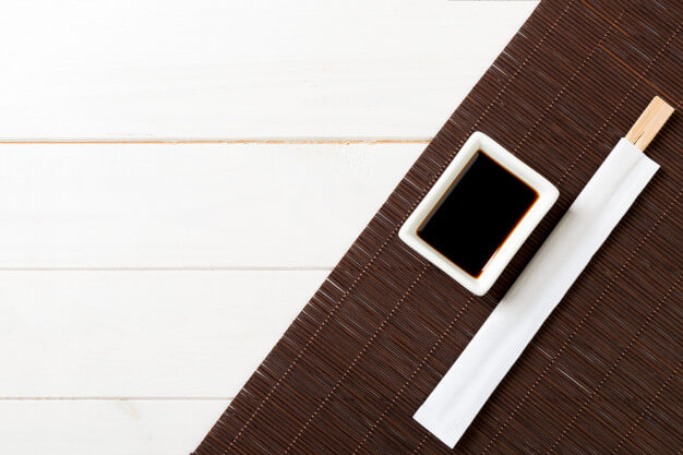Bamboo mat and soy sauce with sushi chopsticks
