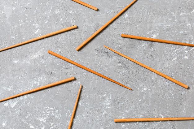 Many bamboo chopsticks on black cement